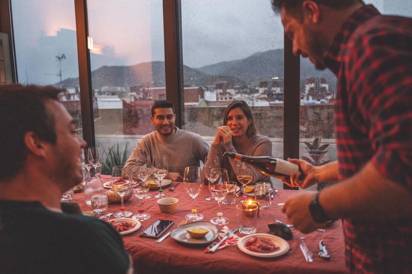 Cata de vinos a domicilio en Bilbao: Ales sirviendo vino en la mesa con los comensales.
